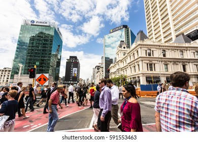 AUCKLAND, NEW ZEALAND - FEBRUARY 22, 2017: Pedestrians cross a street in the busy Auckland central business district in New Zealand largest city on a sunny day.