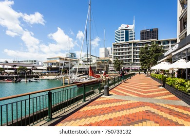 AUCKLAND, NEW ZEALAND - FEBRUARY 22, 2017: A sailboat mooring in the Viaduct marina, lined by restaurants and trendy bars in Auckland's waterfront neighbourhood in New Zealand.