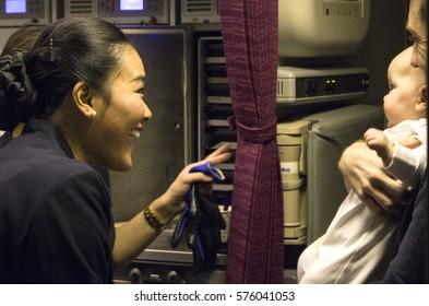 Auckland, New Zealand - February 7, 2017: Flight attendants playing with a baby onboard Boeing 777, Qatar Airways, on the world's longest flight from Doha to Auckland.