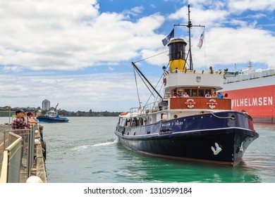 """Auckland / New Zealand - January 26 2019: The """"William C Daldy"""", an Old Steam Tug Built in 1935, Setting Sail on a Passenger Cruise of Auckland Harbour. A Modern Tug is in the Background"""