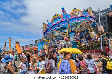 """Auckland / New Zealand - January 27 2019: Amusement Rides. Children on a """"Flying Dragons"""" Ride (a Swing Carousel), Watched by a Large Crowd. Photographed on Auckland Anniversary Weekend"""