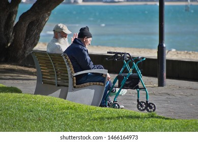 Auckland / New Zealand - July 31 2019: View of two old men sitting on bench at beach with walking frame