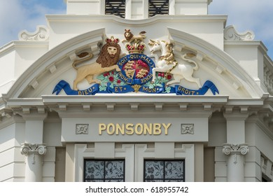 Auckland, New Zealand - March 1, 2017: The cream white mansion with clock tower at intersection of Ponsonby Road and College hill. Closeup of British Royal crest.