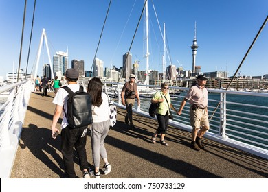 AUCKLAND, NEW ZEALAND - MARCH 1, 2017: People walk across the bascule bridge between the Wynyard Quarter, Auckland's newest and waterfront neighbourhood, and the Viaduct marina in New Zealand.