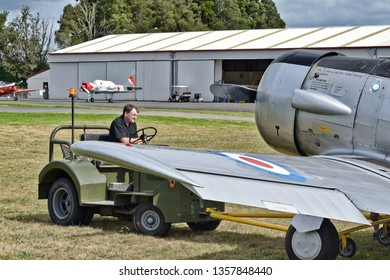 Auckland / New Zealand - March 30 2019: Small vehicle towing NZ Warbirds North American T-6 Texan (Harvard) at Ardmore airport