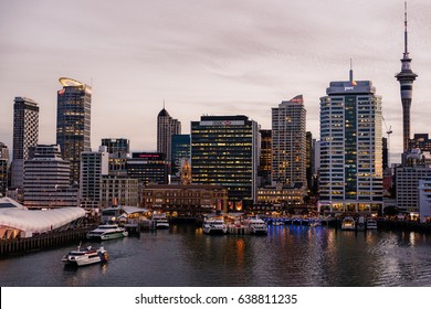 Auckland, New Zealand - March 6, 2017: Ferry building in front of HSBC office building with Sky Tower and a few more high rises in background at sunset. Ferries at docks.