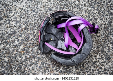 Auckland, New Zealand - May 22 2019: Children's Pink princess bike helmet, purple straps. Crushed by the wheels of a station wagon. Cracked inner and shell. Would do serious damage to a child's head.