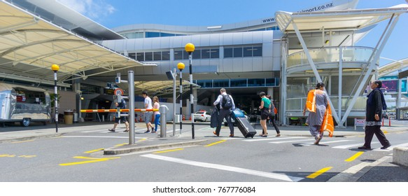 AUCKLAND, NEW ZEALAND - NOVEMBER 23 People including Indian woman in orange sari crossing road towards entrance to international airport terminal November 23, 2017 Auckland New Zealand