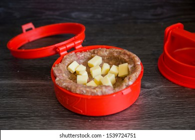 Auckland, New Zealand - November 28 2019: Red plastic burger stuffer. Beef and pork mince patties being stuffed with crispy bacon, chunks of colby cheese. Shows raw ingredients and contraption in use.