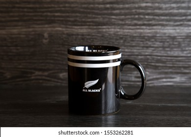 Auckland, New Zealand - October 2 2019: Cup of tea made in an All Blacks cup. All Blacks are one of the best rugby teams in the world. Strong white tea sitting on a dark wood kitchen bench. Fern logo.
