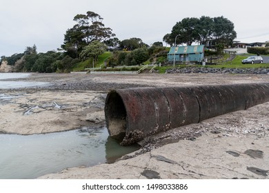 Auckland / New Zealand - September 1 2019: View of concrete storm water pipe on sea bed at low tide with green park in background