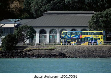 Auckland / New Zealand - September 6 2019: View of Mantells spacious waterside weddings and function venue on Tamaki Drive with  yellow Explorer bus in front