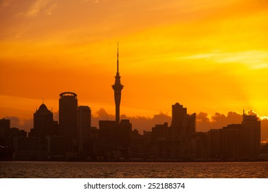 Auckland, New Zealand skyline at sunset with vibrant orange sky and silhouetted buildings.