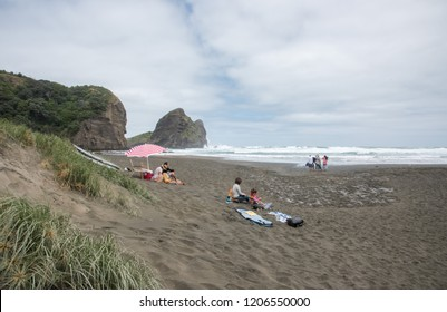 Auckland, North Island, New Zealand-December 17,2016: People picnicking at the black sand Piha Beach with coastal rock and the Tasman Sea in Auckland, New Zealand