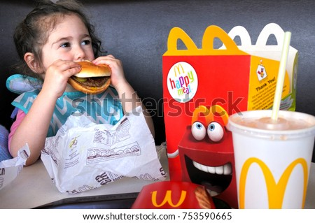 AUCKLAND - NOV 12 2017:Little girl (Naomi Ben-Ari age 03) eats fast food. Fast food is highly processed and contains large amounts of carbohydrates, added sugar, unhealthy fats, and salt (sodium).