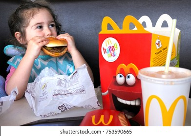 AUCKLAND - NOV 12 2017:Small girl (Naomi Ben-Ari age 03) eats fast food. Fast food is highly processed and contains large amounts of carbohydrates, added sugar, unhealthy fats, and salt (sodium).