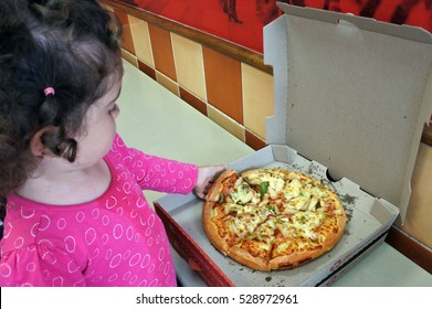 AUCKLAND - NOV 30 2016:Child (Naomi Ben-Ari age 2) eats fast food Pizza.Studies shows that over the past four decades, Fast foods especially among children and adolescents raised the risk of obesity