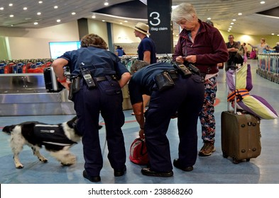 AUCKLAND, NZL - NOV 22 2014:Biosecurity officers with sniffer dog on duty.New Zealand has very strict biosecurity procedures at airports and ports to prevent the introduction of pests and diseases.