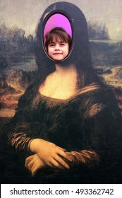 "AUCKLAND - OCT 05 2016:Child (Talya Ben-Ari age 6) smile in a cut out  face of The Mona Lisa painting by Leonardo da Vinci, acclaimed as ""the best known work of art in the world""."