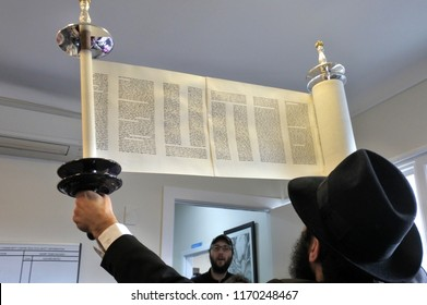 AUCKLAND - SEP 02 2018: Jewish Rabbi holding up a Torah scroll DURING Inauguration of a new Torah scroll ceremony.It is a handwritten copy of the Torah, the holiest book in Judaism