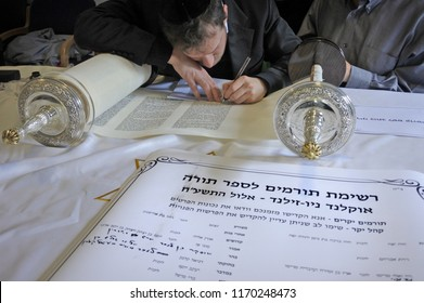 AUCKLAND - SEP 02 2018: Jewish people writing the last letters of the scroll during Inauguration of a new Torah scroll ceremony. It is a handwritten copy of the Torah, the holiest book in Judaism