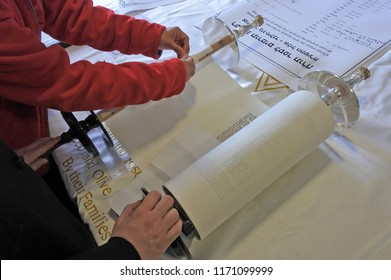 AUCKLAND - SEP 02 2018:Jewish woman sewing the last page of the scroll during Inauguration of a new Torah scroll ceremony. It is a handwritten copy of the Torah, the holiest book in Judaism.