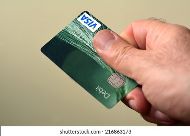 AUCKLAND - SEP 2014:Man hands out debit card.Debit cards are the most profitable sector of the American banking industry, with more than $30 billion in profits per year.