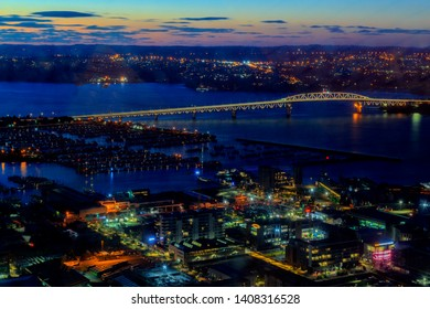 AUCKLAND/NEW ZEALAND - APRIL 13, 2019:  Auckland cityscape panoramic view with lighting Auckland Harbor Bridge against twilight sky shooting from Sky Tower