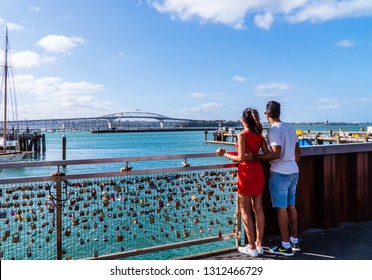 Auckland/New Zealand - Jan 2019: Happy couple admiring the view of Auckland bridge, at harbour. Shot at the love lock gates on the pier in Auckland, North Island, New Zealand. Romantic date, in love,