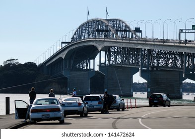 AUCKLAND,NZ - JUNE 02:Fishermen under Auckland Harbour Bridge on June 02 2013.It has a length of 1,020 m (3,348Ã?Â??ft), with a main span of 243.8 m, rising 43.27 m above high water.