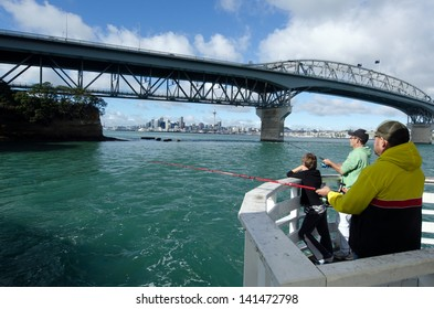 AUCKLAND,NZ - May 26:Fishermen under Auckland Harbour Bridge on May 26 2013. It has a length of 1,020 m (3,348Ã?Â??ft), with a main span of 243.8 m, rising 43.27 m above high water.