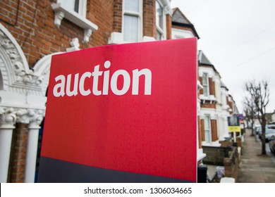 An auction sign on typical street of British terraced houses