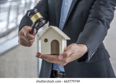 Auctioneer knocking down a property sale holding a model house as he holding gave in hand, or a lawyer or judge mediating in a property dispute in court