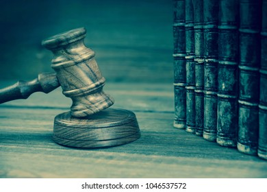 Auctioneers Or Judges Gavel Or Hammer And Old Shabby Books On The Wooden Judge Or Auctioneer Table. Law, Auction Bidding, Judicial Practice Or Judicial Hearing Concept, Close Up. Front View.