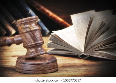 Auctioneers Or Judges Gavel Or Hammer And Stack Of Many Old Shabby Books On The Wooden Judge Or Auctioneer Table. Law, Auction Bidding, Judicial Practice Or Judicial Hearing Concept, Close Up.