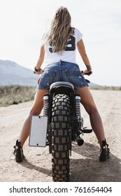 audacious beautiful young woman riding motorbike, camera looks at her back, spirit of freedom and adventure