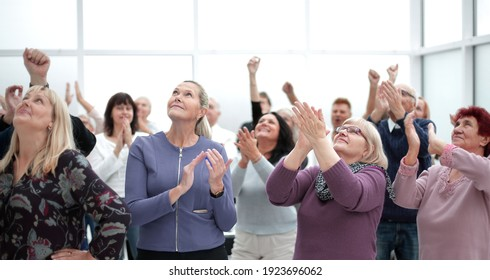 Audience applaud with raised hands in the meeting