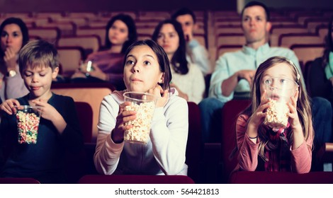 Audience attending movie night with popcorn in cinema house