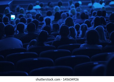 Audience in the cinema. Silhouette shot from back in blue light.