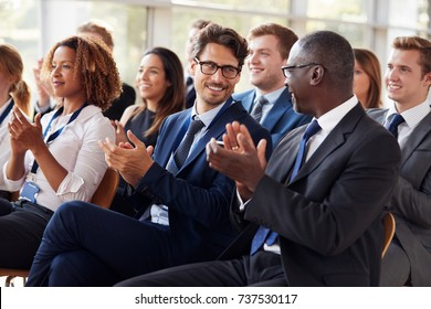 Audience clapping at business seminar, looking at each other