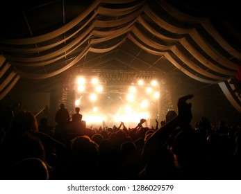 Audience Clapping Hands in Warm Toned Music Tent