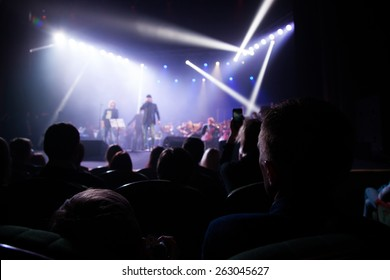 The audience at a concert on background of scene.