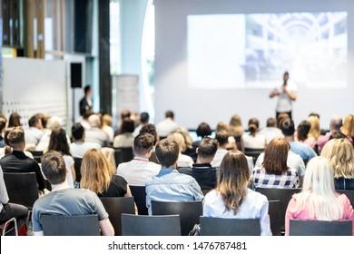 Publikum im Konferenzsaal. Männlicher Redner, der im Konferenzsaal bei geschäftlichen Veranstaltungen spricht. Konzept der Unternehmen und des Unternehmertums. Konzentrieren Sie sich auf nicht erkennbare Menschen im Publikum.
