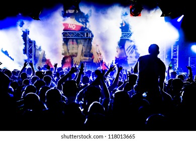 Audience Crowd Man on Shoulders Silhouette Dancing to DJ Pete Tong at Cream Nightclub Party. Nightlife Lazer Show Hands In Air With Smoke Cannon Blast