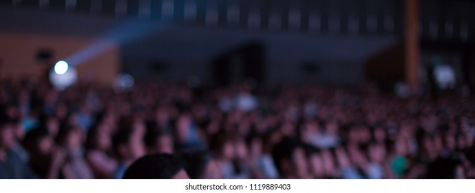Audience, Fans, Spectators, People Watching a Presentation Show Lecture in Auditorium Conference Hall Theater. Crowded Movie House with Many People.  Performance Exhibition. Blurred De-focused Bokeh.