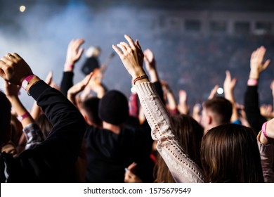 Audience with hands raised at a music festival and lights streaming down from above the stage. Soft focus, high ISO, grainy image.