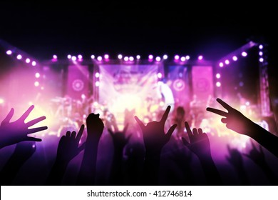 Audience with hands raised at a music festival from above the stage at live concert luxury party.