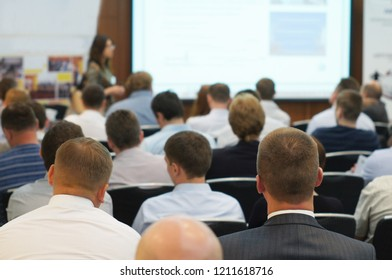 The audience listens to the acting in a conference hall. Focus is under the man on the frontground