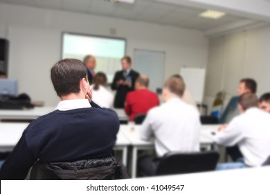 The audience listens to the acting in a conference hall. Focus is under the man on the front ground