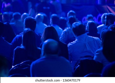 Audience listens to the lecturer at the business conference, back view, blue tones